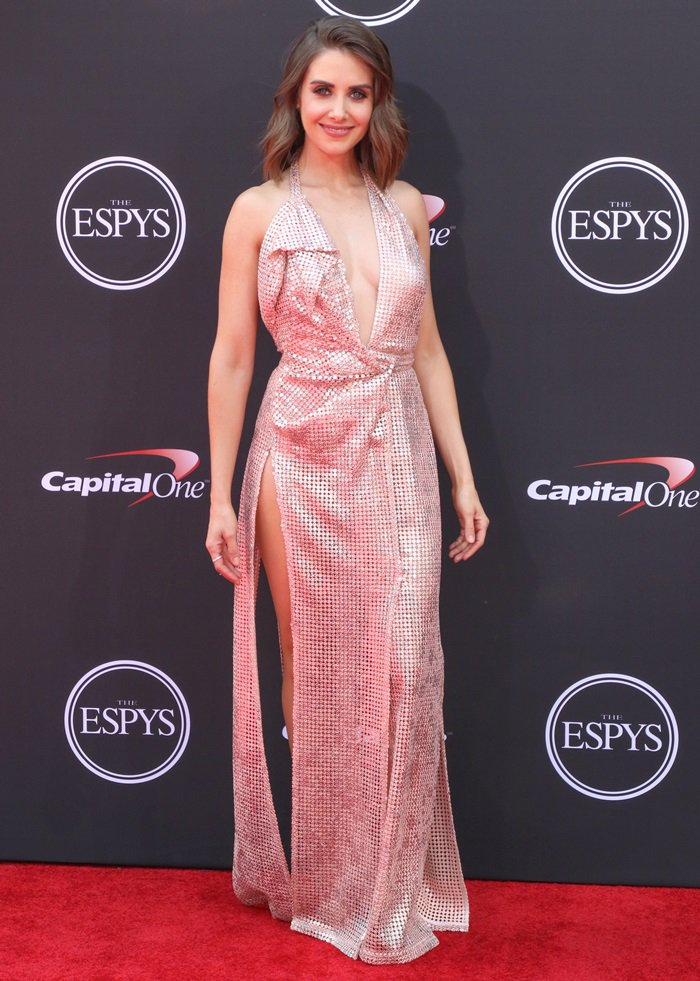 Alison Brie in a Vivienne Westwood Couture sequin column halter dress with plunging neckline and thigh-high slit