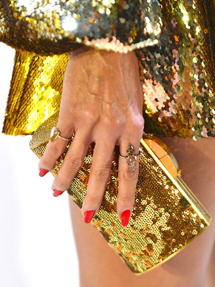 Details of Heidi Klum's gold sequined clutch against her Greta Constantine gold sequined dress.