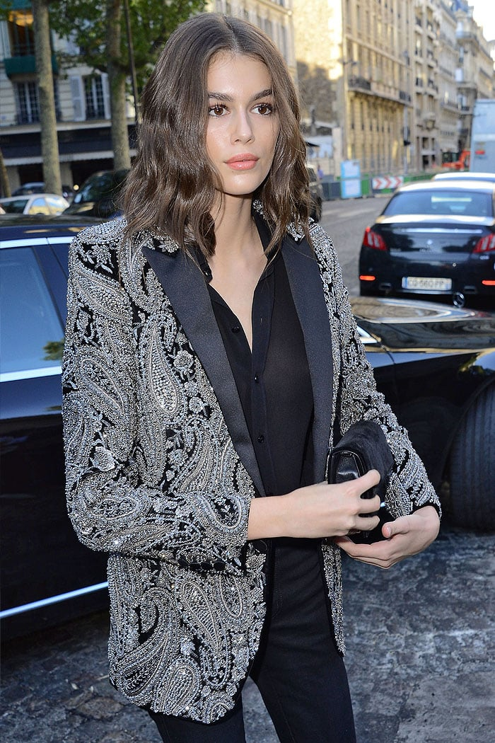 Kaia Gerber braless in a Saint Laurent Spring 2019 Menswear sheer black top and embroidered jacket