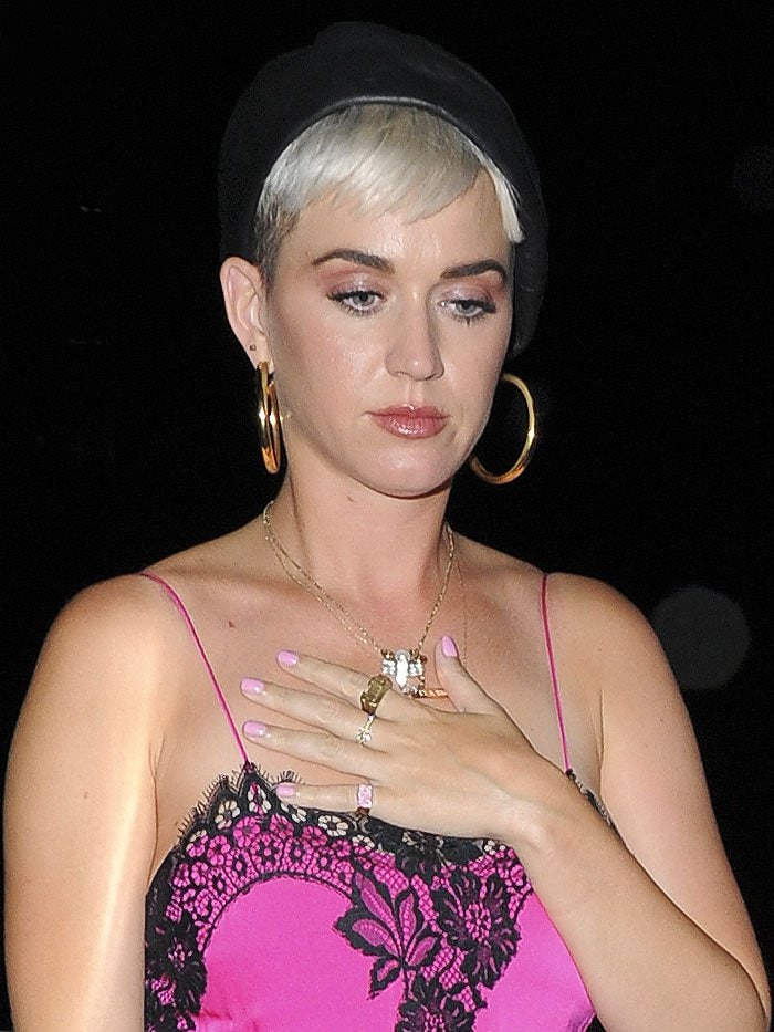 Katy Perry wearing a scorpion necklace, gold hoop earrings, and a black beret.