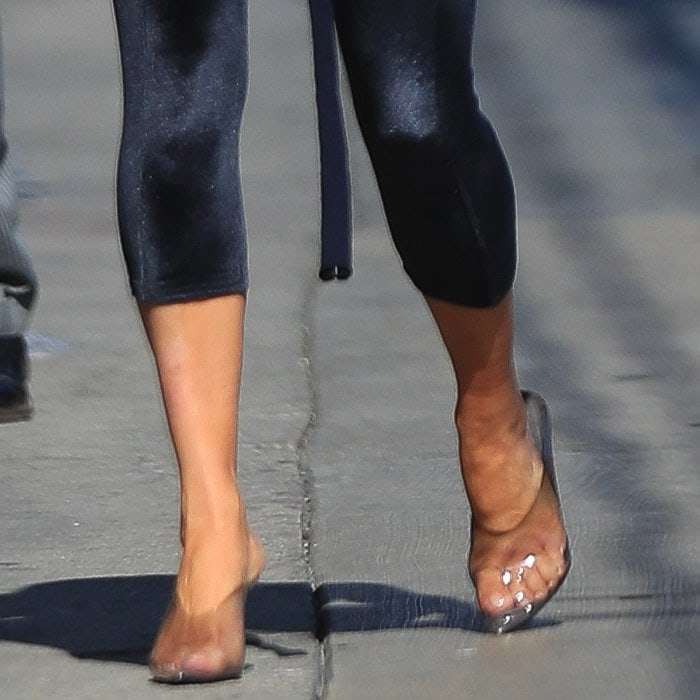 Kim Kardashian showing off her feet in clear mules created by her husband Kanye West