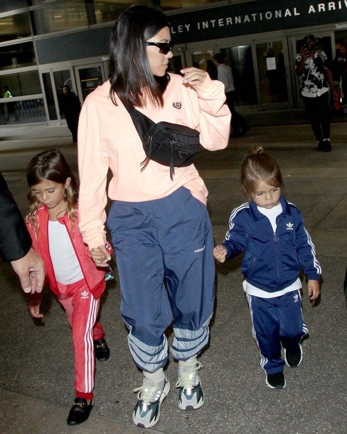 e7db280ccb603 Kourtney Kardashian wearing a neon orange long-sleeved Yeezy  Calabasas   sweatshirt and Kanye West s adidas Yeezy Boost 700 Wave Runner sneakers