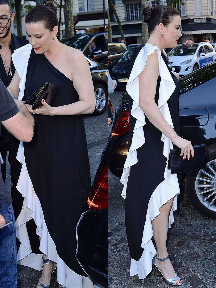 Liv Tyler in a Givenchy Spring 2019 black-and-white ruffled one-shoulder gown with metallic silver ankle-strap sandals.