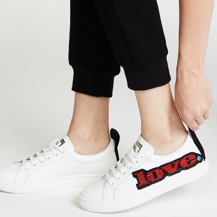 "Made from white leather with a black contrast heel tab, the low-top design boasts positive messaging at the side: the word ""love"" is spelled out in sparkling crystals"