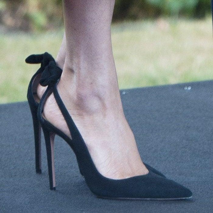 Meghan Markle wearing black Deneuve bow pointy toe pumps byAquazzura