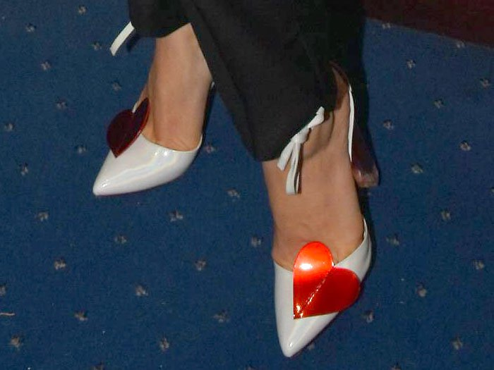 Melissa George in white-patent ankle-tie pumps with red hearts and red-tinted chunky clear heels.