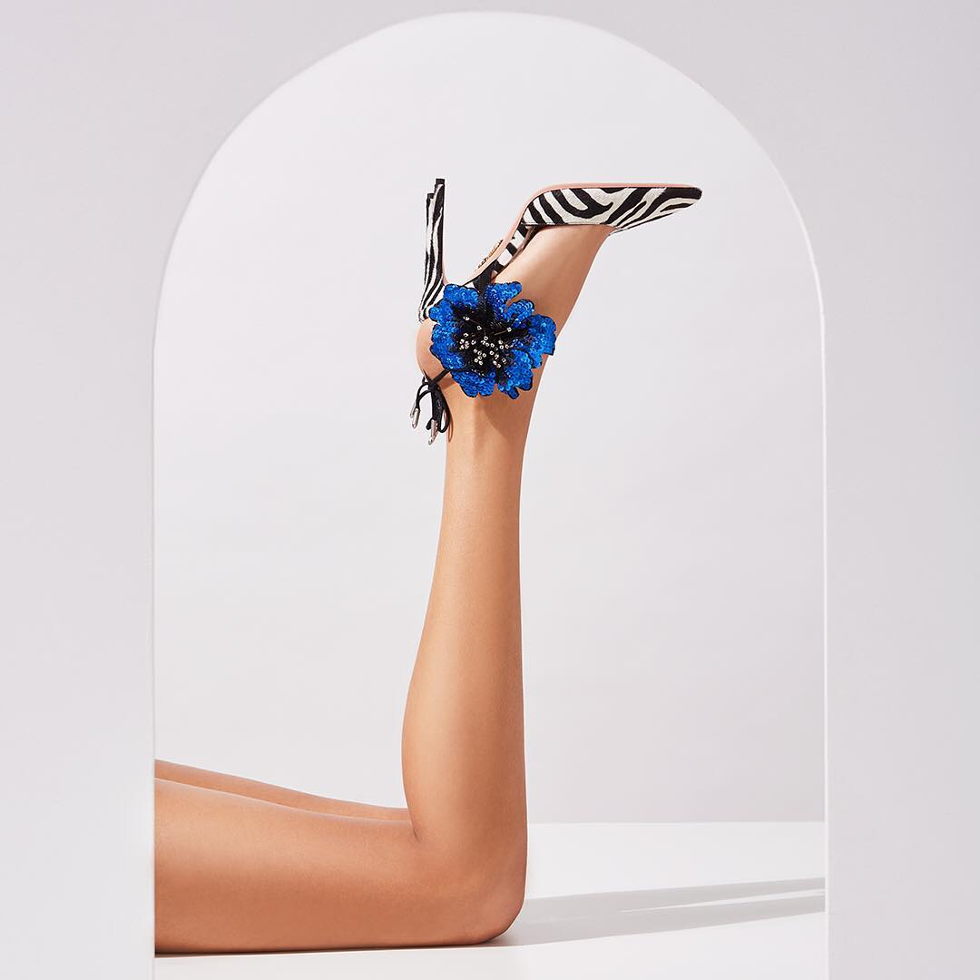 Boasting a zebra print, these eye-catching pumps feature an elegant pointed toe, a branded insole, a secure back tie fastening, a high stiletto heel and a stunning sequin floral embellishment