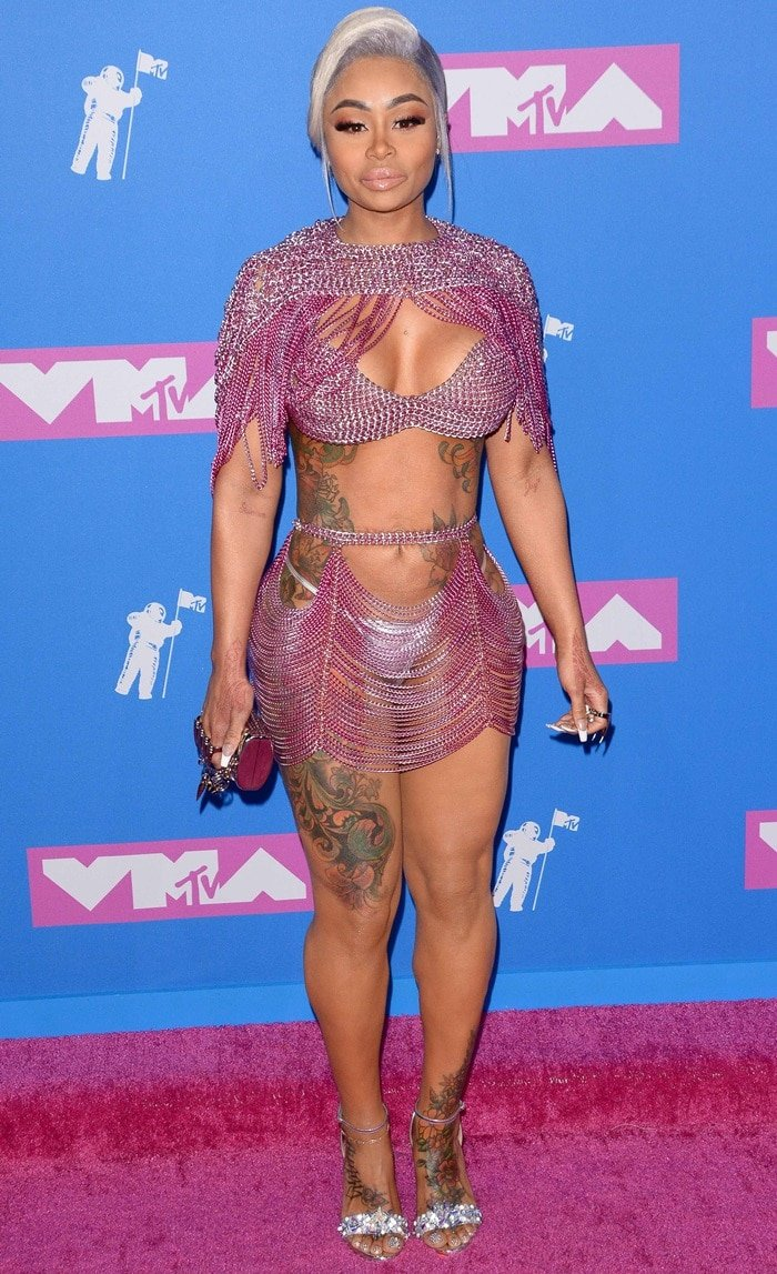 Blac Chyna shows off her numerous body tattoos in a pink chain link dress with pink makeup