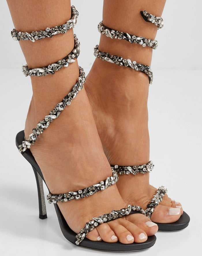 Crafted in Italy from lustrous black leather with shimmering flecks, this pair is embellished with contrasting crystals along the coiled strap that delicately winds around your ankle