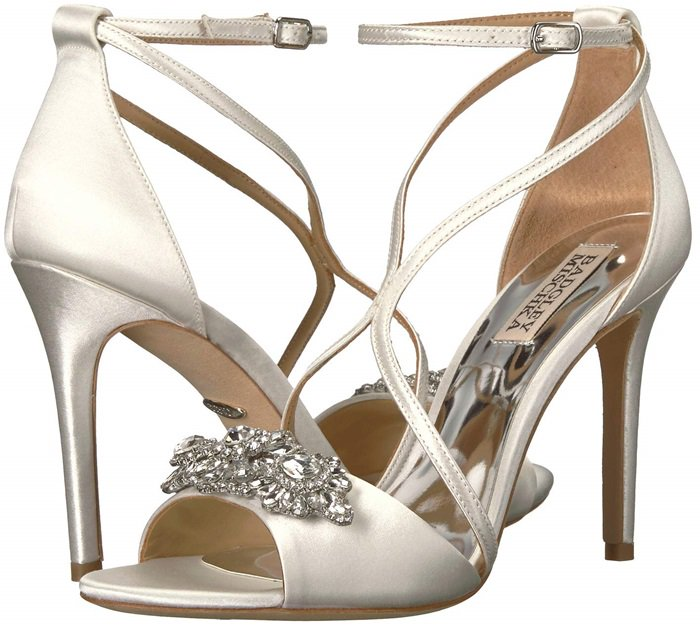 A brilliant crystal brooch sparkles on a lustrous satin sandal styled with graceful, curving straps