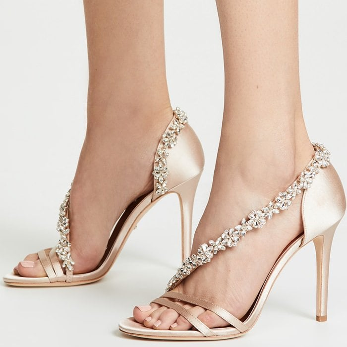 An eye-catching array of faceted crystals traces a sparkling path across the open vamp and around the heel of a striking satin sandal lifted by a towering stiletto