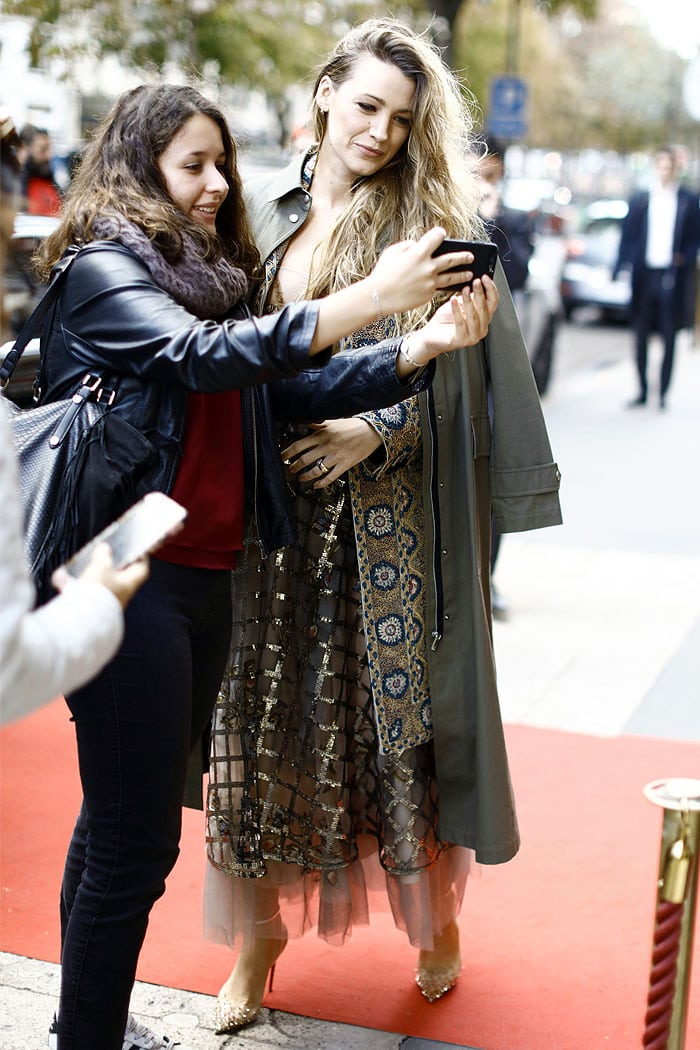 Blake Lively taking a selfie with a fan outside the Christian Dior Spring 2019 fashion show