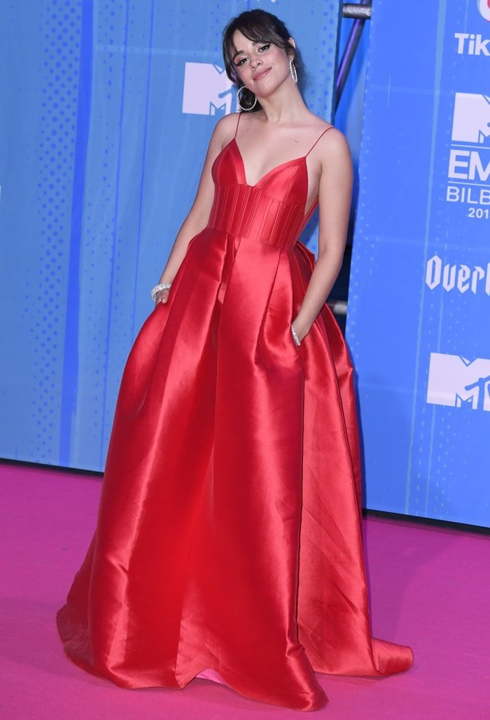 Camila Cabello in a red Alex Perry dress featuring a v-neckline with a fitted bodice and a pleated skirt