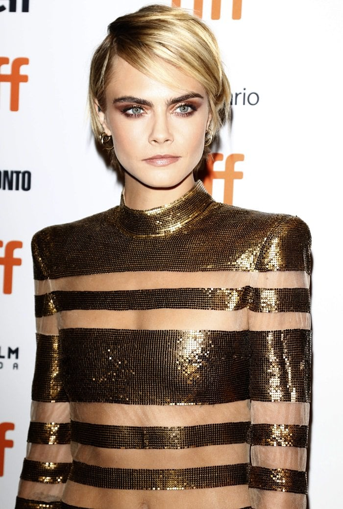 Cara Delevingne's metallic mini dress features risqué sheer paneling throughout