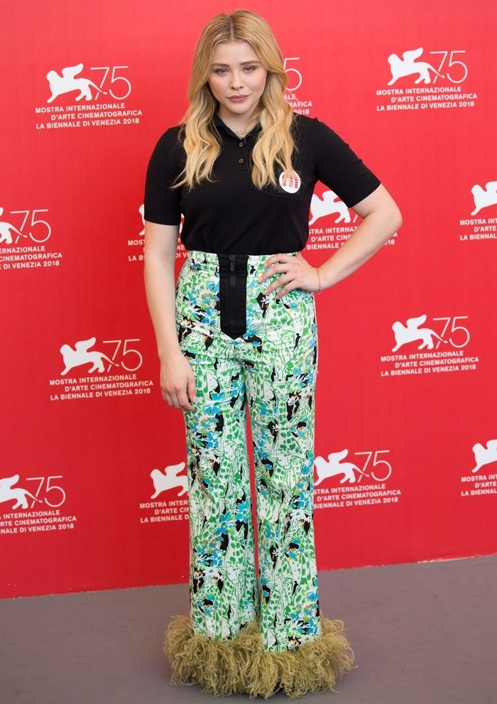 Chloe Grace Moretz in an outfit from the Miu Miu Resort 2019 Collection consisting of a black top and printed pants with embroidery