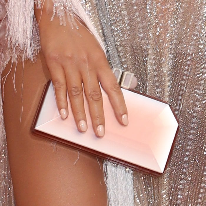 Chrissy Teigen toting a Judith Leiber Couture clutch in faceted acrylic