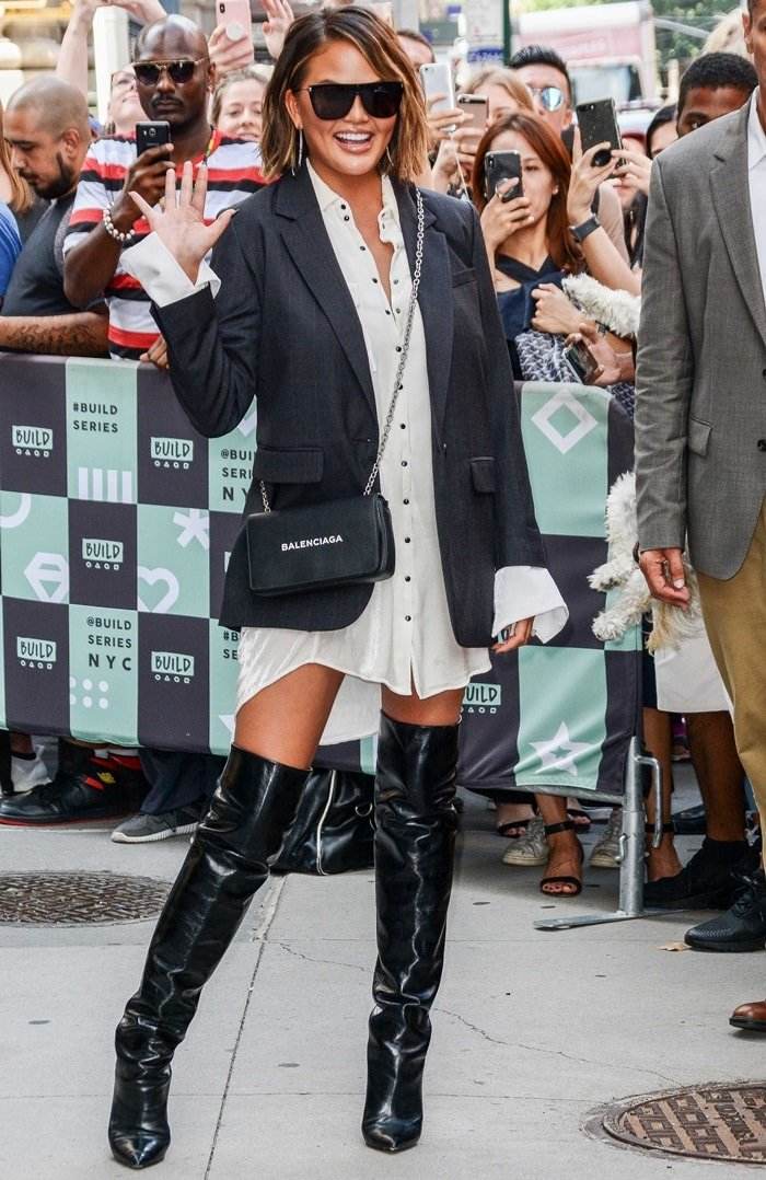 Chrissy Teigen wearingher favorite 'Niki' glossed-leather knee boots witha white button-down dress