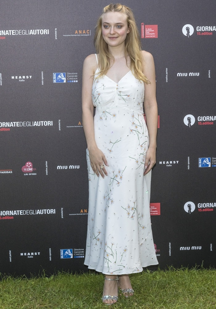 Dakota Fanning wearing a white floral slip dress from Miu Miu