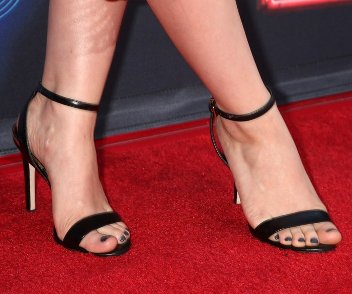 Dove Cameron's bare feet in simple black ankle-strap sandals