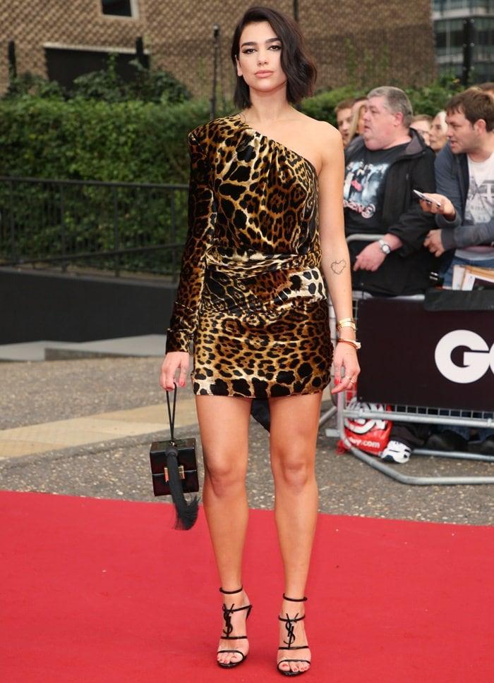 Dua Lipa highlights her gorgeous legs in a one-shoulder leopard print dress