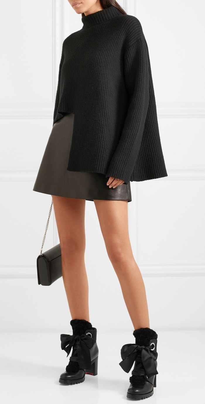Model wearing a 'Vallauris' asymmetric merino wool-blend turtleneck sweater from Kym Ellery with a bow-embellished leather mini skirt from Miu Miu