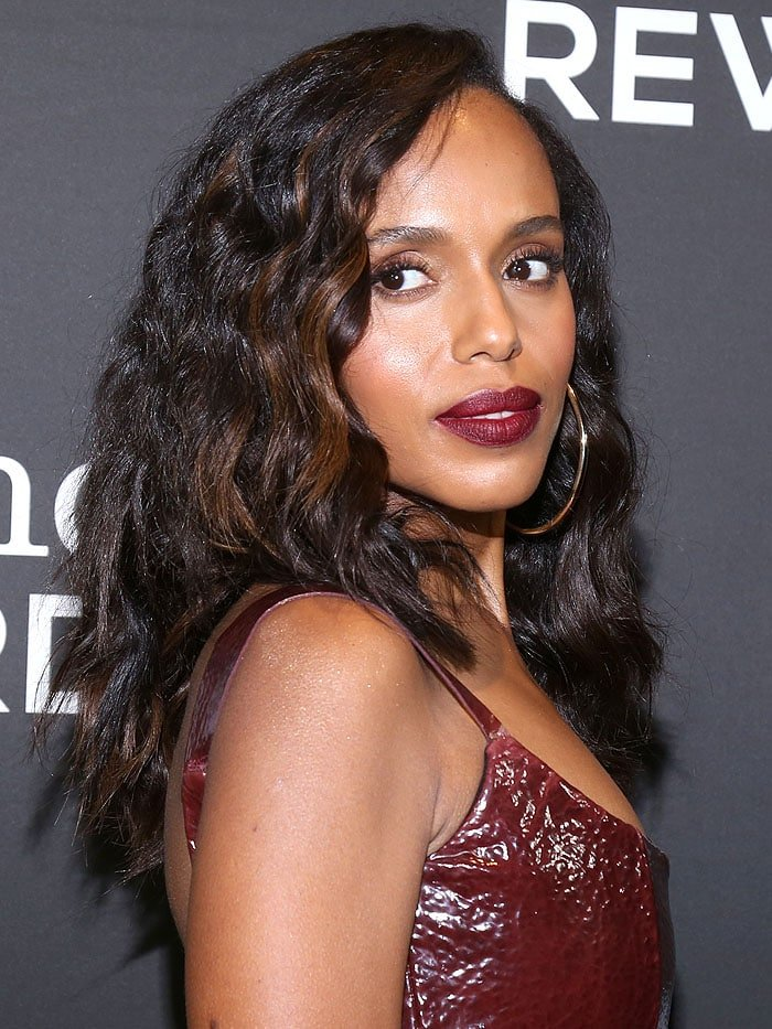 Kerry Washington wearing a Markarian Fall 2018 leather dress, gold hoop earrings, wine-red lipstick, and chunky brown highlights in her wavy hair.