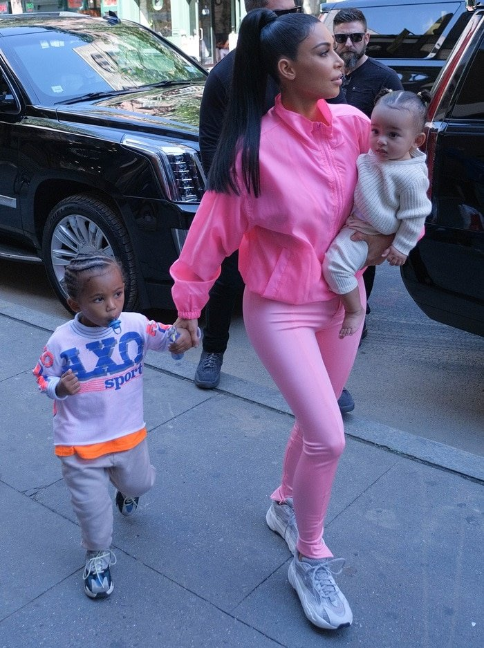 Kim Kardashian with Chicago in her arms and Saint holding her hand
