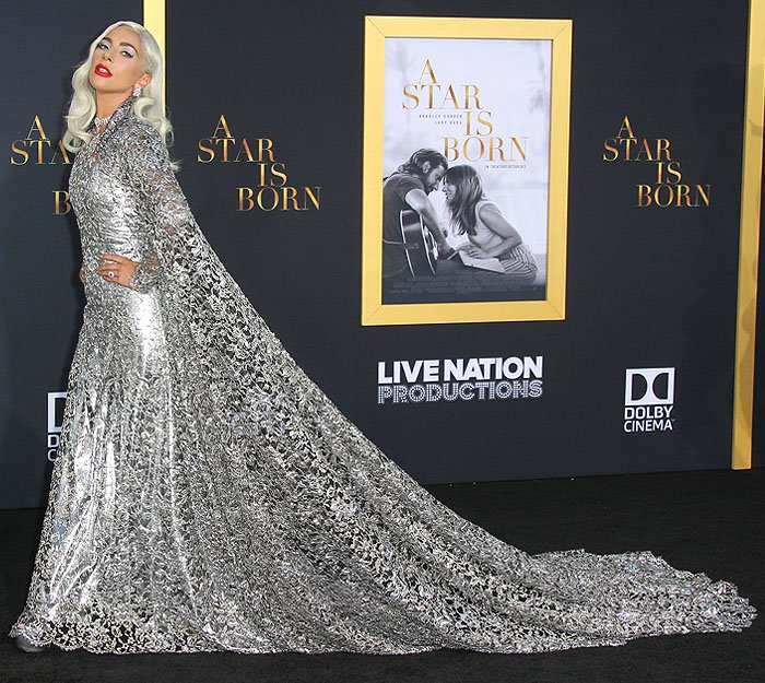 Lady Gaga wearing a Givenchy Haute Couture silver cape gown, silver platform sandals, and Bulgari jewelry.