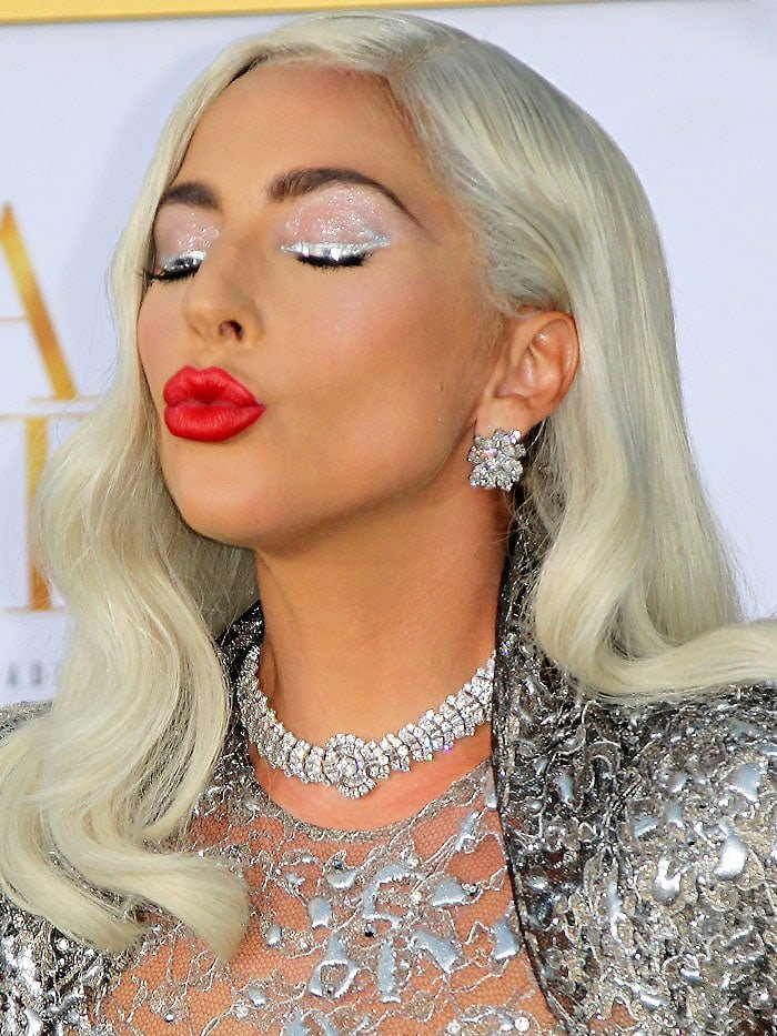 Lady Gaga making a kissy face with red lips.