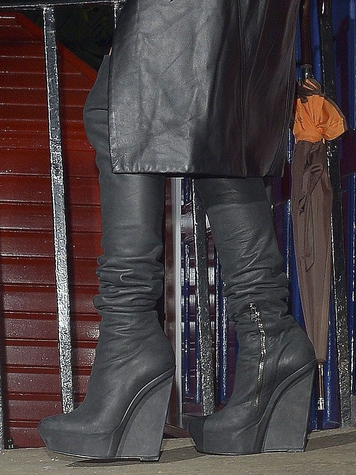 Lady Gaga navigating stairs in Gareth Pugh slouchy wedge-platform thigh-high boots