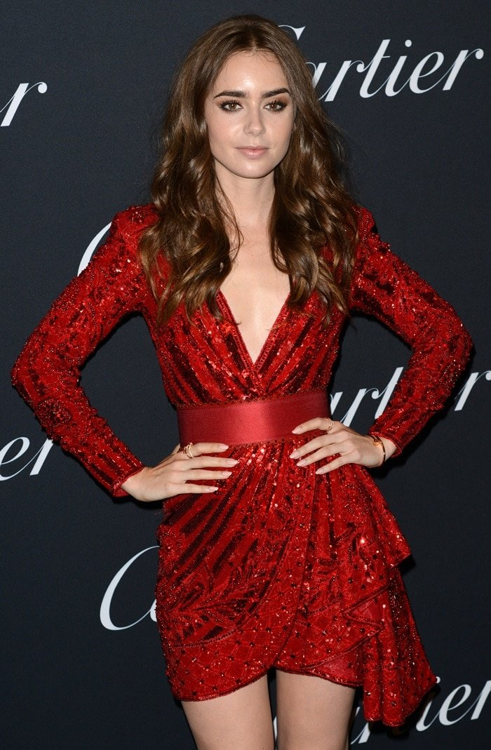 Lily Collins rocking a vibrant red dress while attending the Cartier Juste Un Clou New York Event held at Cartier Mansion in New York City on September 6, 2018