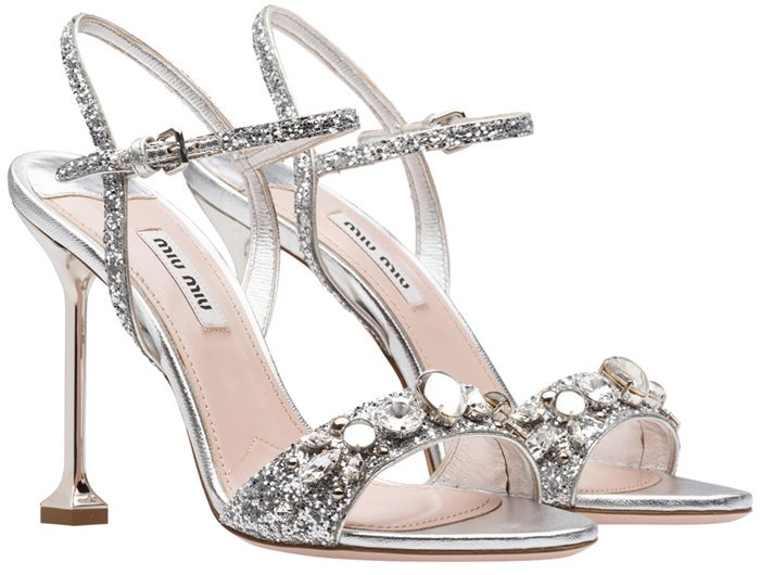 Crafted in Italy from metallic silver calf leather, these glittered sandals from Miu Miu feature a high stiletto heel, an ankle strap with a side buckle fastening, a branded insole, an open toe and Swarovski crystal embellishments