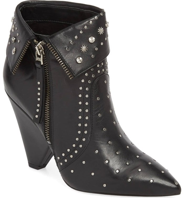 A constellation of studs wraps the vamp and curls around the asymmetrical cuff of a Western-inspired bootie shaped with a pointed toe and a tapered heel.