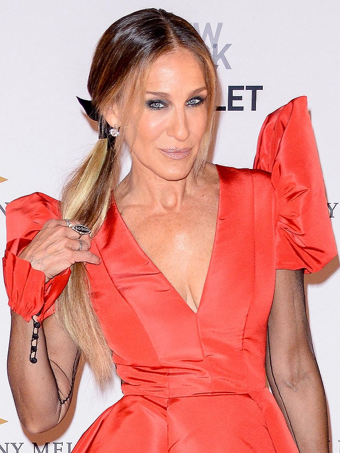 Sarah Jessica Parker wearing a Giles Deacon Couture red ball gown featuring a sheer back, puffed shoulders, seamed sheer sleeves, and Victorian buttons on the ruffled cuffs