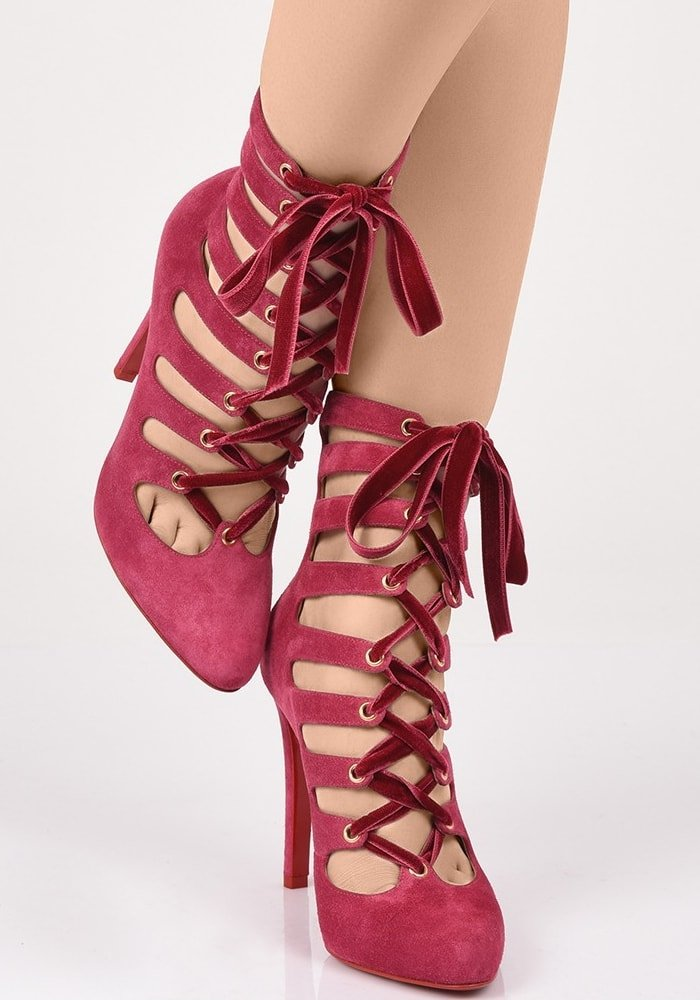 A velvet ribbon beautifully ties together the caged straps of a plush suede bootie set on a slim stiletto heel