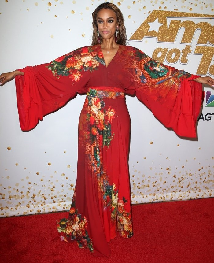 Tyra Banks in a kimono-inspired red dress by Stello
