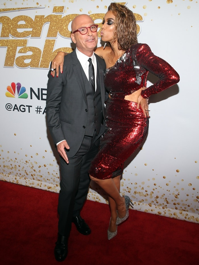 Tyra Banks getting ready to give Howie Mandel a kiss on the red carpet while flaunting her sexy legs