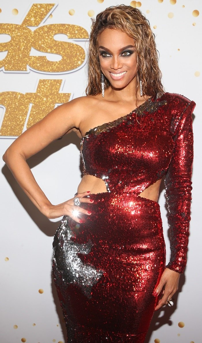 Tyra Banks wearing a silver two-way sequin asymmetrical Usama Ishtay dress