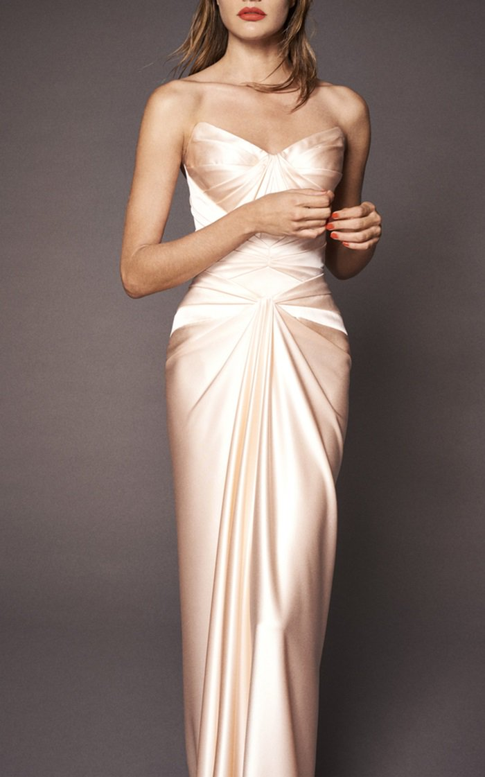 This stunning dress features a pleated bodice with a sweetheart neckline and a draped full-length skirt