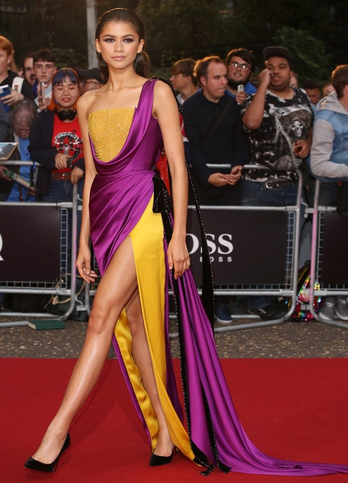 Zendaya looking electricina purple and yellow draped gown that highlighted her legs