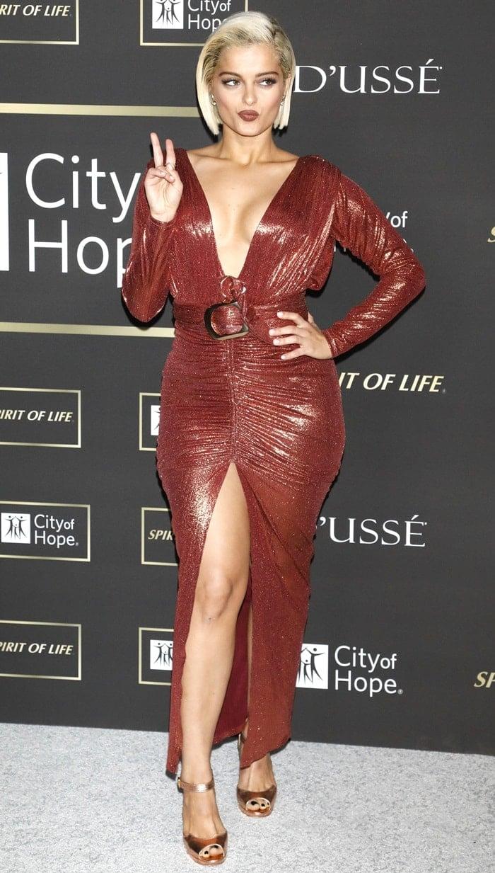 Bebe Rexha flaunts herhot legs in alow-cut shimmery dress by Lena Berisha