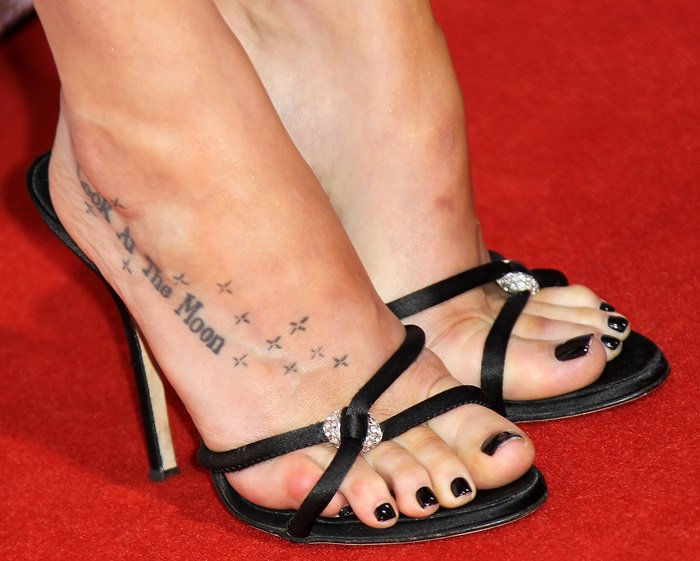 Dakota Johnson has a tattoo which says Look At The Moon surrounded by little stars on her right foot