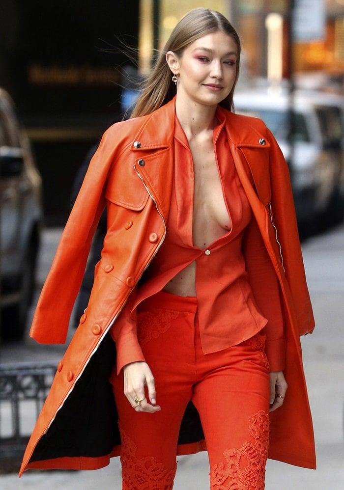 Gigi Hadid reveals sideboob ina custom orange Ronald van der Kemp silk shirt and pants in New York City on December 11, 2018
