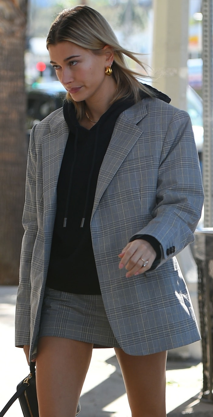 Hailey Baldwin rocks a cool, slouchy crop hoodie with an oversized gray plaid blazer