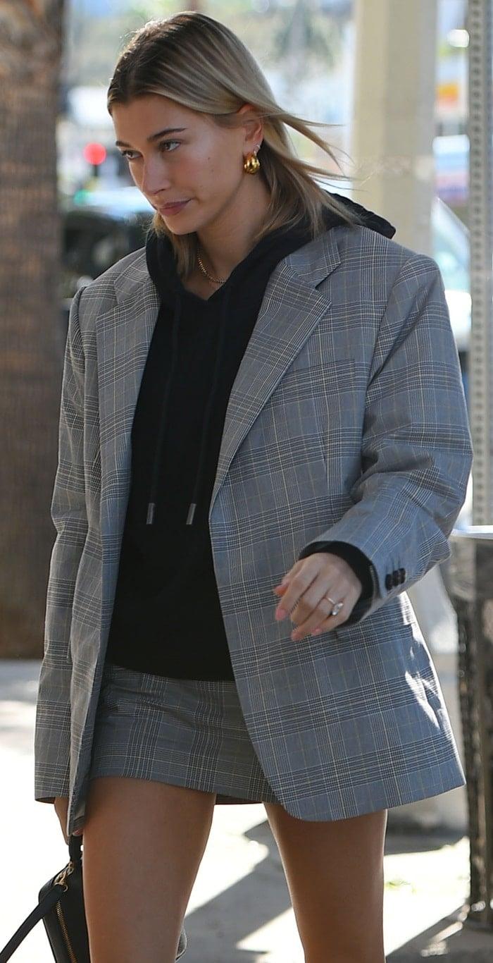 Hailey Baldwin rocks a cool, slouchy crop hoodie with anoversized gray plaid blazer