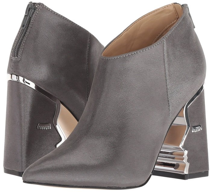 Heeled ankle boots with suede upper featuring face silhouette and hardware detailing