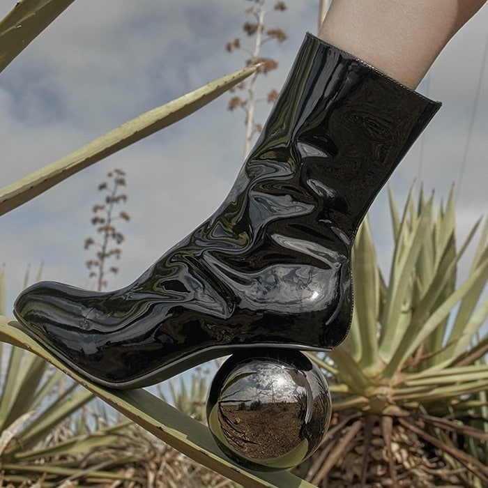 Round-toe leather boot in high-shine patent leather with statement spherical heel