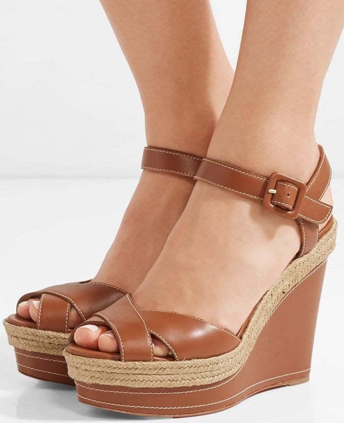Crafted in Spain, this stylish pair features a self-covered platform wedge trimmed with woven raffia