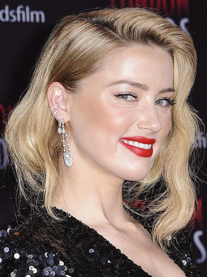Amber Heard wearing diamond ear cuffs, studs, and dangling earrings