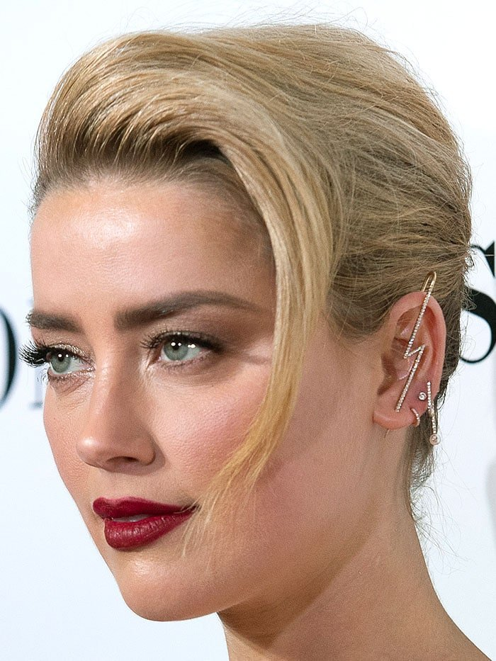 Closeup of Amber Heard's selection of earrings including a gold-and-diamond lightning piercing